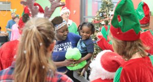 santa and elves with little girl smiling